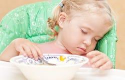 Маленькая девочка упала уснувший на таблице есть суп Стоковые Фото