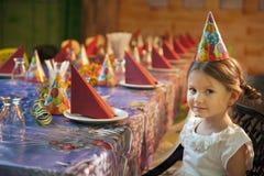 Маленькая девочка усаженная на ее таблицу дня рождения Стоковая Фотография RF
