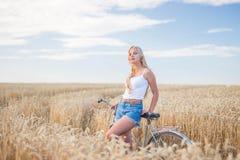 Маленькая девочка усмехается в поле с ретро велосипедом Стоковые Фото