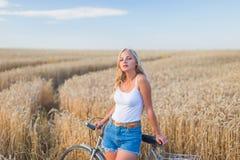 Маленькая девочка усмехается в поле с ретро велосипедом Стоковые Фотографии RF