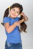 Маленькая девочка усмехаясь и расчесывая волосы Стоковое Изображение RF