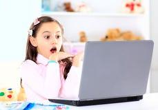 маленькая девочка усмехаясь и смотря компьтер-книжку Стоковое Фото