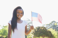 Маленькая девочка усмехаясь на камере развевая американский флаг стоковые изображения rf