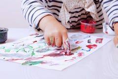 Маленькая девочка уча покрасить развитие ребенка в искусстве Стоковая Фотография