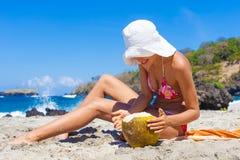 Маленькая девочка фото ослабляя на пляже с кокосом Усмехаясь лето времени холодка траты женщины внешнее Горизонтальное изображени Стоковые Фото
