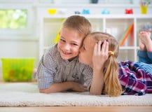 Маленькая девочка целует ее счастливого брата Стоковая Фотография