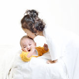 Маленькая девочка целуя младенца Стоковое Фото