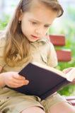 Маленькая девочка читает книгу стоковое изображение rf
