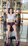 Маленькая девочка для того чтобы сыграть спорт поднимает гантели в спортзале Стоковые Фото