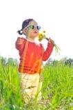 Маленькая девочка outdoors с цветками Стоковые Фото