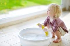 Маленькая девушка малыша помогая ее маме очистить вверх стоковое фото