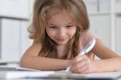 маленькая девушка студента делая домашнюю работу Стоковая Фотография