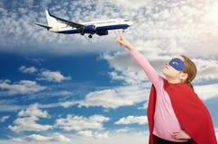 Маленькая девушка супергероя держит самолет с ее пальцем стоковая фотография rf