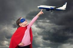 Маленькая девушка супергероя держит самолет с ее пальцем стоковое фото