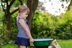 Маленькая девушка хелпера моет одежды в тазе outdoors Стоковые Изображения RF