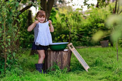 Маленькая девушка хелпера моет одежды в тазе outdoors Стоковая Фотография