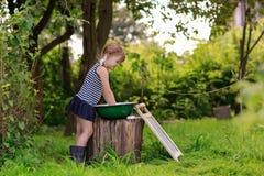 Маленькая девушка хелпера моет одежды в тазе outdoors Стоковое Изображение RF