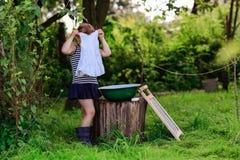 Маленькая девушка хелпера моет одежды в тазе outdoors Стоковые Изображения