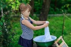 Маленькая девушка хелпера моет одежды в тазе outdoors Стоковое Фото