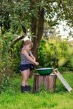 Маленькая девушка хелпера моет одежды в тазе outdoors Стоковые Фотографии RF