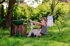 Маленькая девушка хелпера моет одежды используя washboard outdoors Стоковое Изображение RF