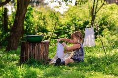 Маленькая девушка хелпера моет одежды используя washboard outdoors Стоковая Фотография RF