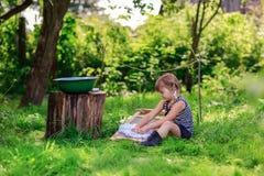 Маленькая девушка хелпера моет одежды используя washboard outdoors Стоковая Фотография