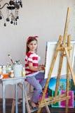 Маленькая девушка художника держа paintbrush и рассматривая canva Стоковая Фотография