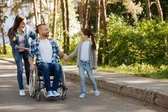 Маленькая женская персона стоя около ее инвалидного отца стоковые изображения