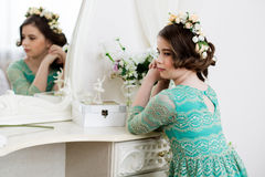 Маленькая задумчивая девушка в венке цветка сидит на шлихте Стоковые Фото