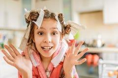 Маленькая изумленная девушка с curlers волос на ее голове Стоковые Изображения