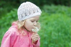 Маленькая кавказская девушка держа и дуя на белом стручке одуванчика Стоковые Изображения RF