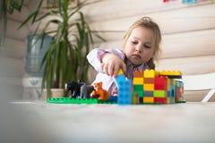 Маленькая кавказская девушка играя конструктора на таблице, Стоковое Фото