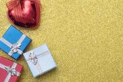 3 маленькая коробка и сердце рождества сформировали красный шарик на желтой предпосылке Стоковое фото RF