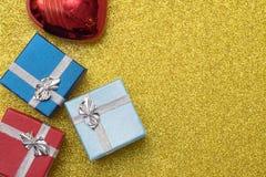 3 маленькая коробка и сердце рождества сформировали красный шарик на желтой предпосылке Стоковое Фото