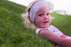 Маленькая красивая девушка лежит на зеленой траве Стоковая Фотография