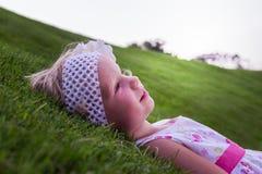 Маленькая красивая девушка лежит на зеленой траве Стоковые Изображения RF