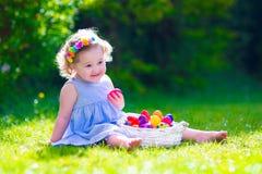 Маленькая красивая девушка на охоте пасхального яйца Стоковые Изображения RF