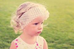 Маленькая красивая девушка сидя на зеленой траве Стоковая Фотография