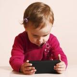 Маленькая красивая девушка с ее умным телефоном Стоковые Изображения RF