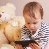 Маленькая красивая девушка с умным телефоном на предпосылке Bea Стоковые Фотографии RF