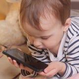 Маленькая красивая девушка с умным телефоном Стоковые Изображения RF