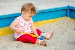 Маленькая красивая игра младенца девушки в ящике с песком и песке забавляется на спортивной площадке Стоковые Изображения RF