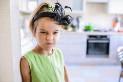 Маленькая красивая неудовлетворенная девушка в зеленом платье стоковое фото