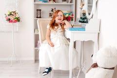 Маленькая красная с волосами девушка в белом платье Стоковое фото RF