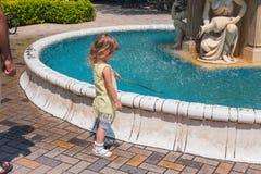 Маленькая курчавая белокурая девушка играя outdoors Стоковые Изображения RF