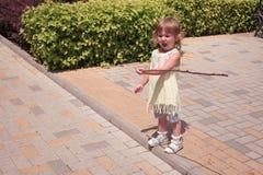 Маленькая курчавая белокурая девушка играя outdoors Стоковое фото RF
