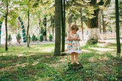 Маленькая курчавая белокурая девушка играя outdoors Стоковые Фотографии RF