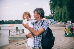 Маленькая курчавая девушка и ее отец outdoors Стоковые Изображения RF