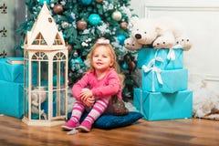 Маленькая курчавая усмехаясь девушка стоя почти рождественская елка Стоковое фото RF